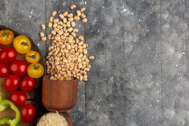Vista superior, feijão, espalhado, juntamente, com, vermelho, e, amarela, tomates, ligado, a, cinzento, rústico, chão