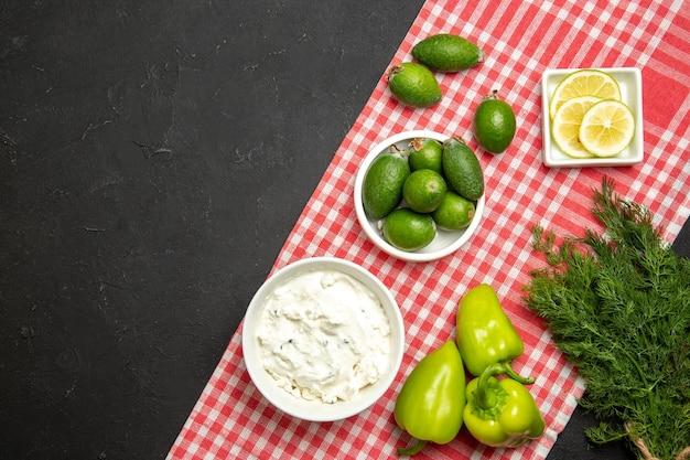 Vista superior feijoa fresca com creme de limão e pimentão verde na superfície escura da cor do produto de farinha de frutas