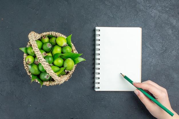 Vista superior feijoas frescas em lápis de caderno de cesta em mão feminina em superfície escura