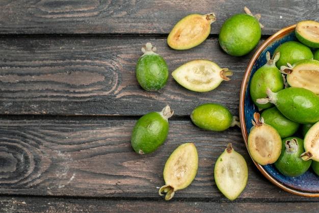 Vista superior feijoas verdes frescas dentro do prato na mesa rústica de madeira foto colorida de frutas suco azedo maduro espaço livre