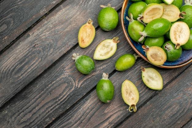 Vista superior feijoas verdes frescas dentro do prato na mesa rústica de madeira foto colorida de frutas suco maduro azedo