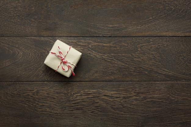 Vista superior feliz ano novo festival ou aniversário e feliz natal conceitual background.hands segurando o pequeno presente.objeto na moderna madeira marrom rústica na mesa do escritório em casa com cópia espaço.