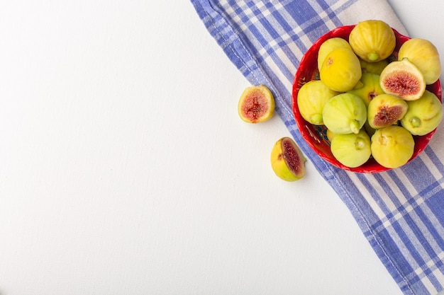 Vista superior figos frescos doces deliciosos fetos dentro de uma placa vermelha na mesa branca