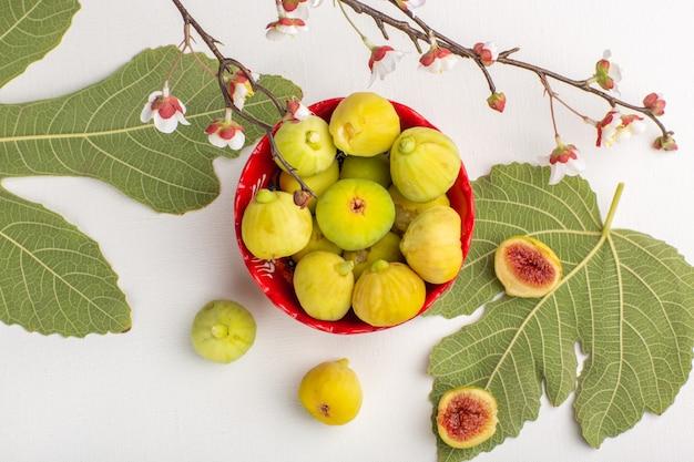 Vista superior figos frescos doces deliciosos fetos dentro de uma placa vermelha na superfície branca Foto gratuita