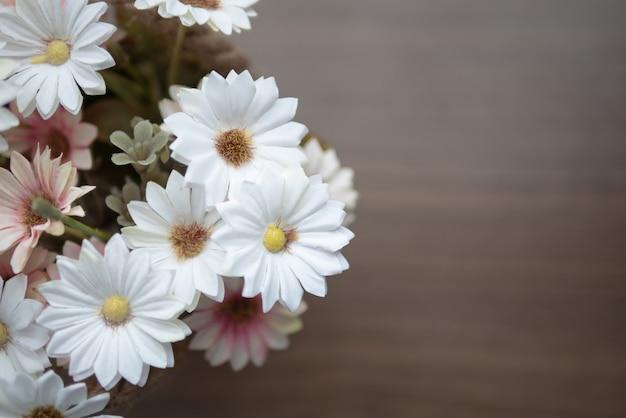 Vista superior, florescendo de flor falsa na mesa de madeira