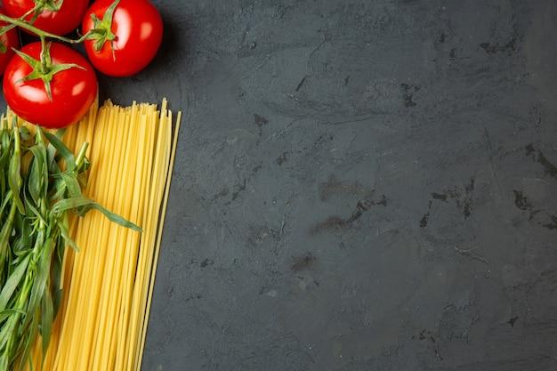 Vista superior fo espaguete cru e tomate fresco com espaço de cópia no preto