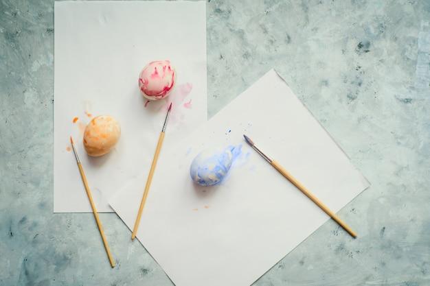 Vista superior foco seletivo pintado ovos de páscoa e pincéis em uma tabela