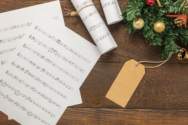 Vista superior folha de música papel de nota e decoração de natal em fundo de madeira