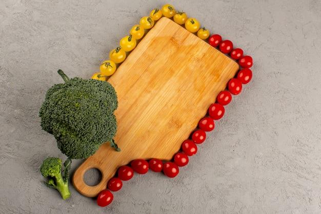 Vista superior forrada tomates juntamente com brócolis verde sobre fundo cinza