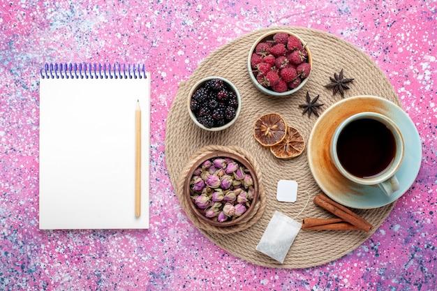 Vista superior, framboesas e amoras frescas com uma xícara de chá e canela em fundo rosa.
