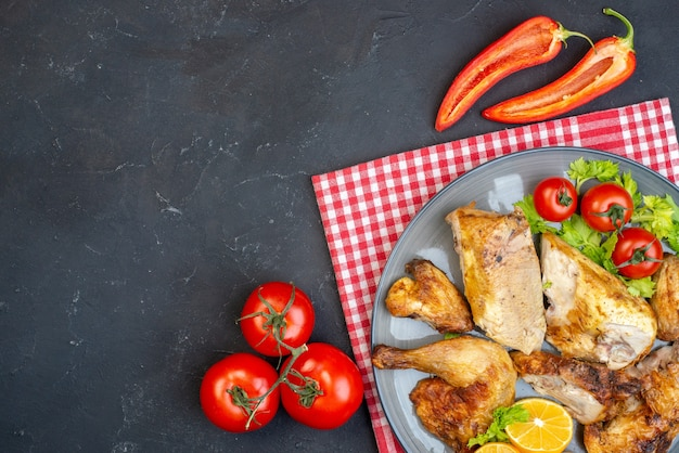 Vista superior, frango assado, rodelas de limão no prato, tomate, pimenta, pimenta preta