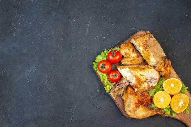 Vista superior frango assado, tomate, rodelas de limão na placa de madeira no preto