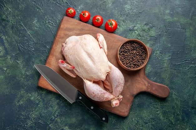 Vista superior frango cru fresco com tomates vermelhos em fundo azul escuro cozinha refeição foto animal comida frango carne cor fazenda