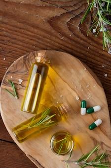 Vista superior frascos com óleo orgânico e comprimidos em cima da mesa