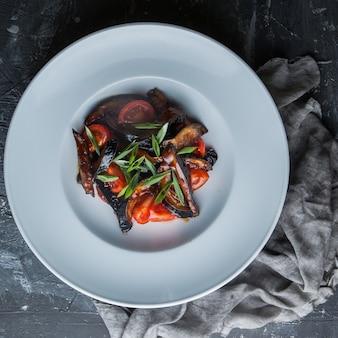 Vista superior frito berinjela com tomate e cebolinha picada e pano no prato branco redondo