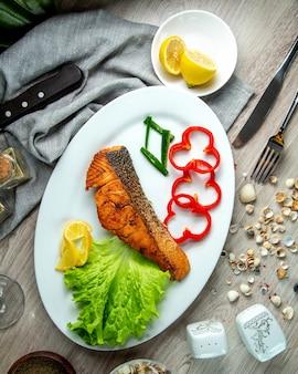 Vista superior frito peixe vermelho com pimentão uma fatia de limão