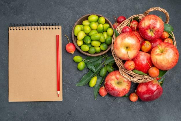Vista superior frutas cítricas cesta de madeira de cerejas maçãs caderno creme lápis vermelho