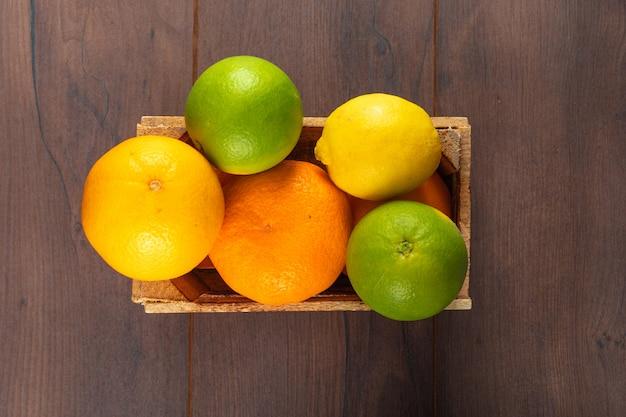Vista superior frutas cítricas em caixa de madeira na mesa de madeira
