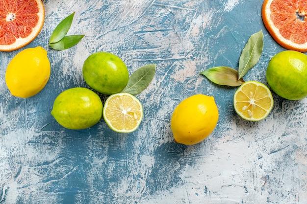 Vista superior frutas cítricas limões toranjas tangerinas na superfície azul e branca