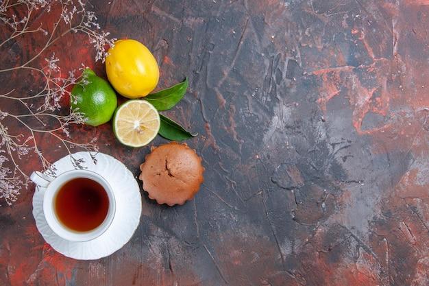 Vista superior frutas cítricas uma xícara de chá limão limão cupcake galhos de árvores