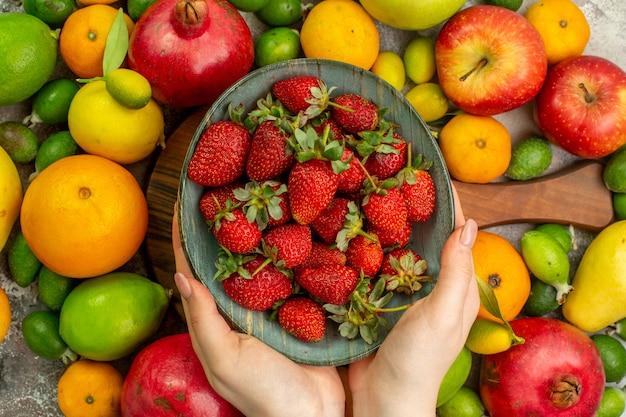 Vista superior frutas frescas diferentes frutas maduras e maduras no fundo branco saúde saborosa foto colorida dieta baga