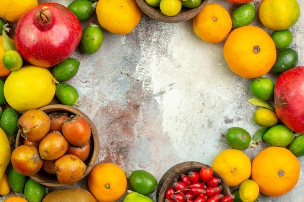 Vista superior frutas frescas diferentes frutas suaves no fundo branco baga madura saborosa cor saúde da árvore