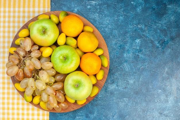 Vista superior frutas frescas maçãs tangerinas e uvas na mesa azul