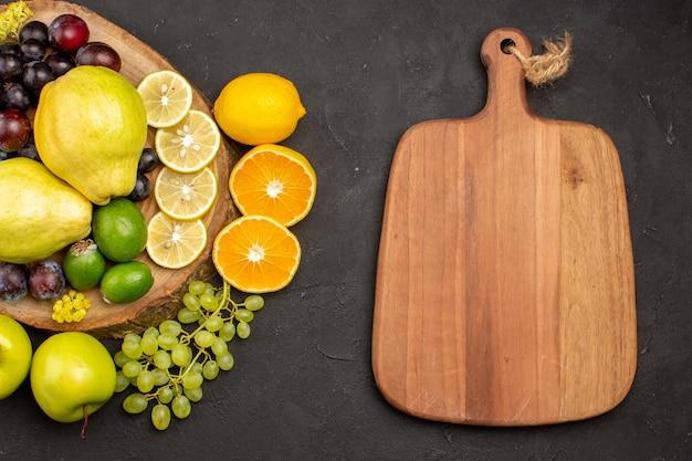 Vista superior frutas frescas uvas rodelas de limão, ameixas e marmelos na superfície escura