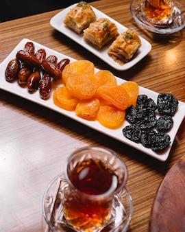 Vista superior frutas secas com baklava turco e um copo de armudu de chá