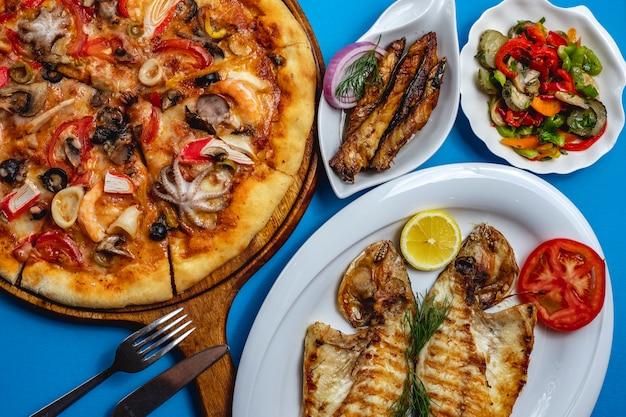 Vista superior frutos do mar mix pizza com cogumelos polvo carne de caranguejo queijo tomate peixe frito com fatia de cebola roxa de limão e salada de legumes em cima da mesa