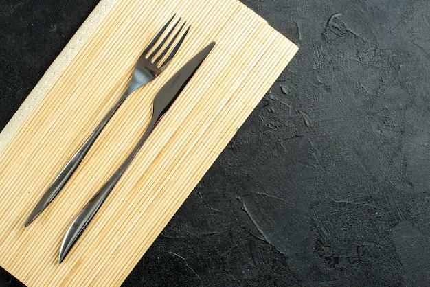 Vista superior garfo e faca na placa de madeira bege no espaço livre da mesa preta