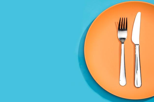 Vista superior garfo e faca no prato com espaço de cópia