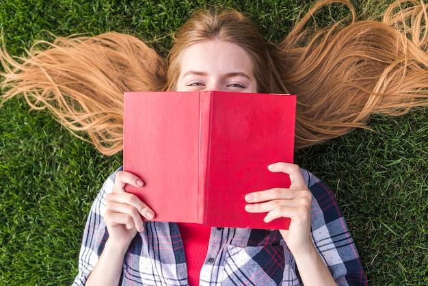 Vista superior garota cobrindo a boca com um livro