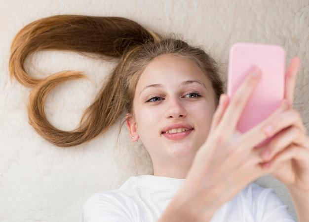 Vista superior garota tomando selfie