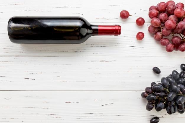 Vista superior garrafa de vinho com cacho de uvas