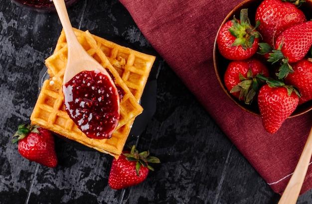 Vista superior geléia de morango e waffles em fundo preto