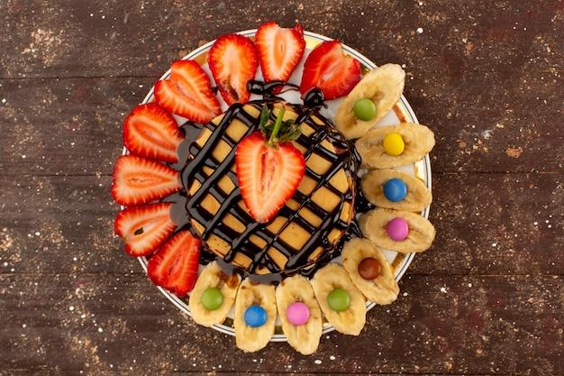 Vista superior gostoso panquecas com frutas na mesa marrom