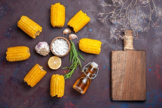 Vista superior grãos amarelos frescos crus com óleo na superfície escura salgadinhos de milho crus frescos