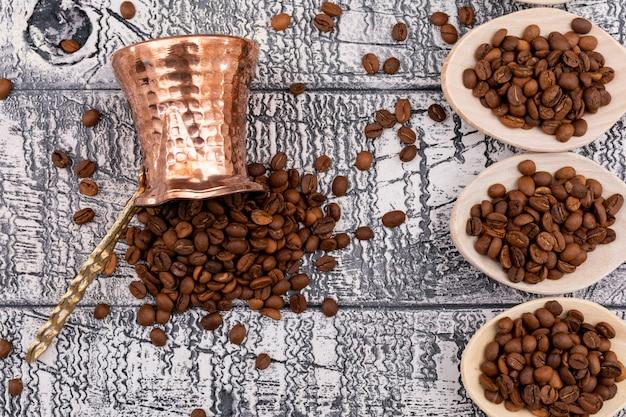 Vista superior, grãos de café, cafeteira e colheres de pau na superfície de madeira