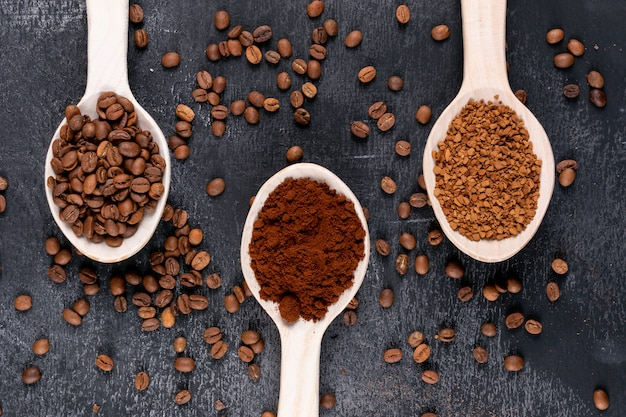 Vista superior, grãos de café e café instantâneo em colheres de madeira na superfície escura
