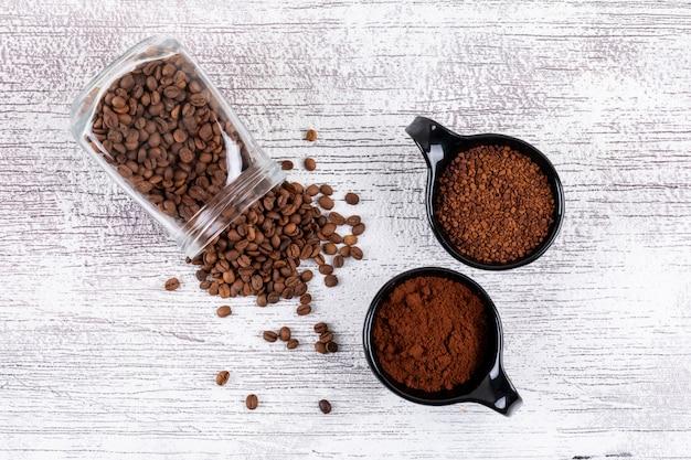 Vista superior grãos de café e café instantâneo na mesa branca