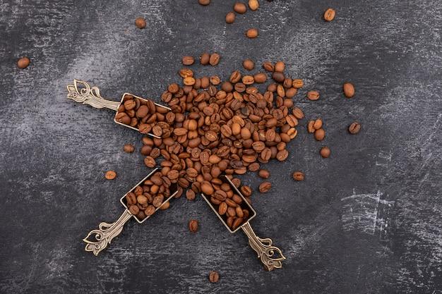 Vista superior, grãos de café em colher de metal na superfície escura