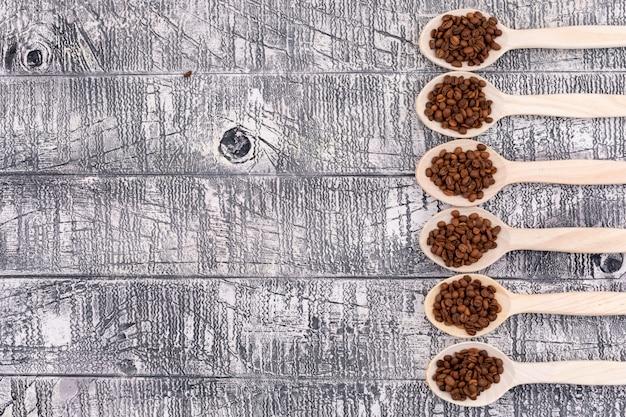 Vista superior, grãos de café em uma colher de madeira diferente na superfície de madeira branca