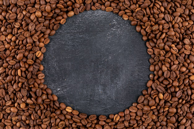 Vista superior grãos de café na superfície escura