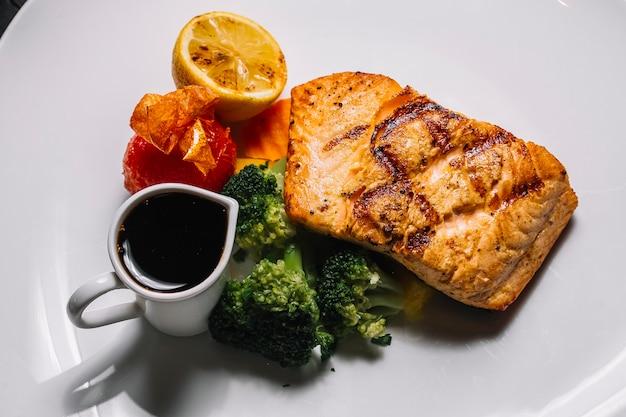 Vista superior grelhada posta de peixe vermelha com brócolis, uma fatia de limão tomate e molho narsharab