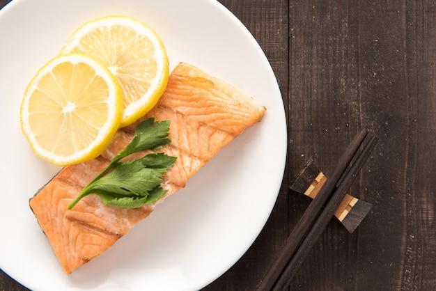 Vista superior grelhado salmão com limão no prato.