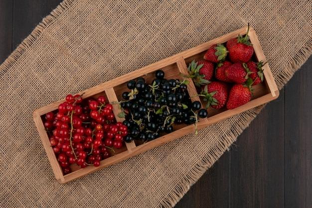 Vista superior groselha vermelha e preta com morangos em um fundo de madeira
