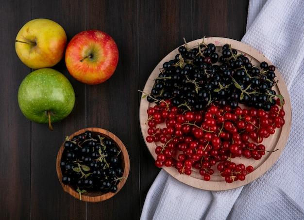 Vista superior groselha vermelha e preta em uma toalha de cozinha com maçãs em um fundo de madeira