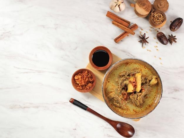 Vista superior gule kambing jawa timur ou east java lamb curry, menu delicioso para eid al adha. normalmente servido com sate kambing (espetos de carneiro), espaço para texto