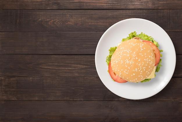 Vista superior hambúrguer de churrasco no prato branco sobre fundo de madeira. copie o espaço para o seu texto